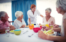 caregiver and group of elderly seniors in the dining table