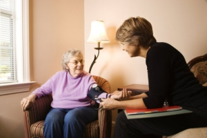 nurse checks on an elderly woman's blood pressure