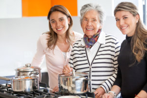 caregivers helping an elder woman in the kitchen