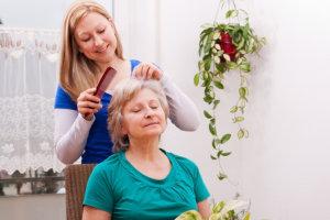 caregiver brushing the hair of an elder woman