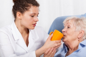 nurse gives something to drink old woman