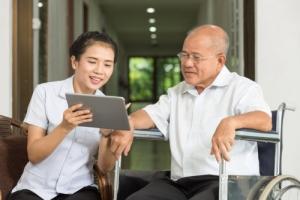 caregiver showing tablet to elderly man