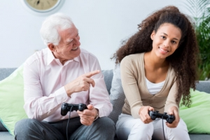 an old man and caregiver playing video games each other
