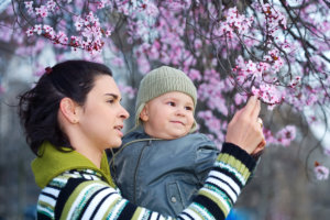 caregiver and the baby enjoy the early spring between flowers